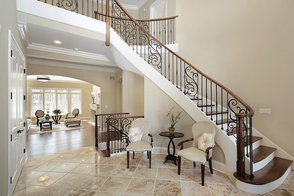 This foyer features beige tiles flooring and beige walls, along with a staircase with hardwood steps and iron railings.