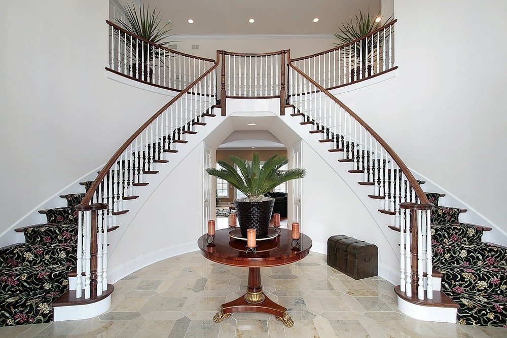 This foyer boasts a glamorous staircase with elegant carpet steps. The area features tiles flooring and a high ceiling, along with a fancy centerpiece table.