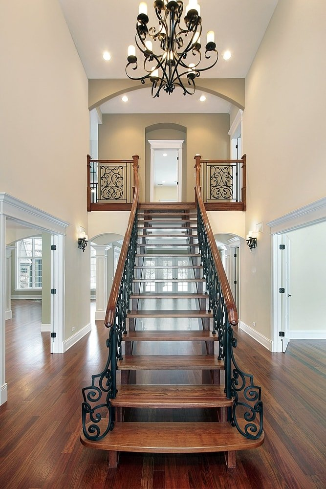 A focused look at this foyer's gorgeous straight staircase with elegant railings, lighted by a jaw-dropping chandelier hanging from the home's high ceiling