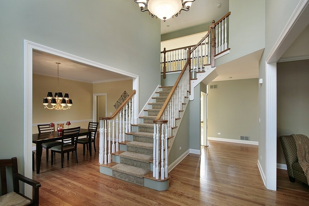 A foyer area featuring hardwood floors and gray walls, along with a two-storey ceiling lighted by a gorgeous ceiling light.