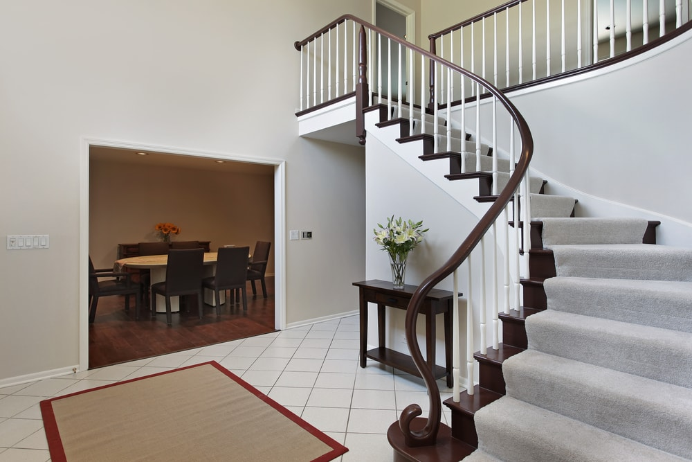 This foyer features tiles flooring topped by an area rug and is surrounded by light gray walls. It offers a winder staircase with carpeted steps.
