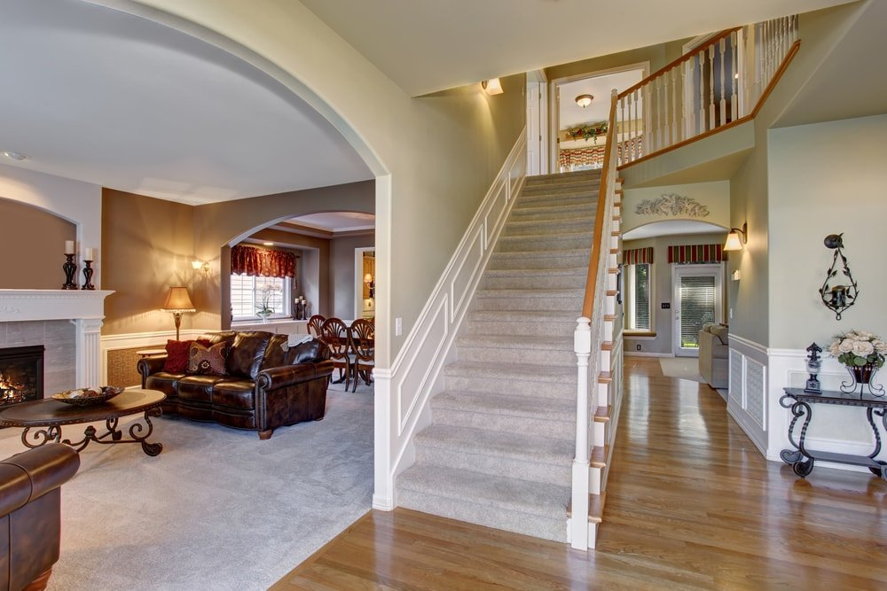 This foyer features a straight staircase leading to the home's second floor. The home's living space is set on the side, featuring a set of leather seats and a fireplace.