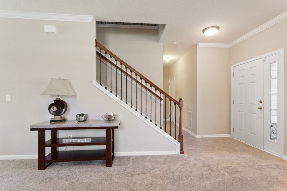 A spacious foyer boasting carpeted flooring, beige walls and a regular ceiling. There's a straight staircase leading to the home's second floor.