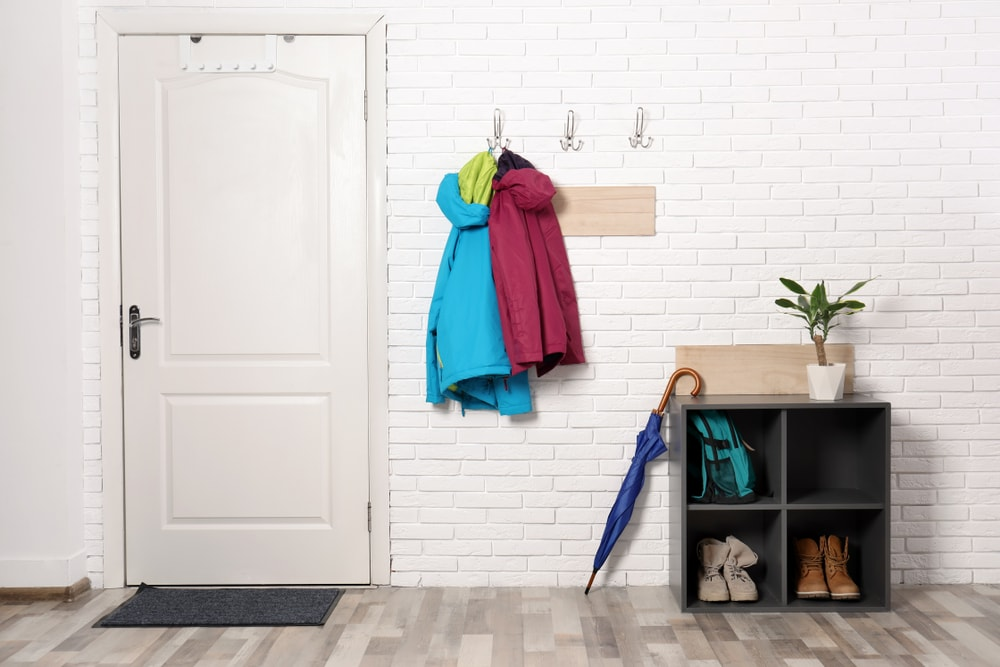 This mudroom features a white brick wall and stylish hardwood flooring. The area also has a box-type modern shoe rack on the side.