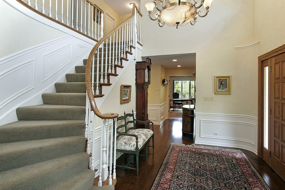 A small foyer featuring hardwood flooring and an area rug. The area is surrounded by beige walls. There's a staircase with carpeted steps and a charming ceiling light.