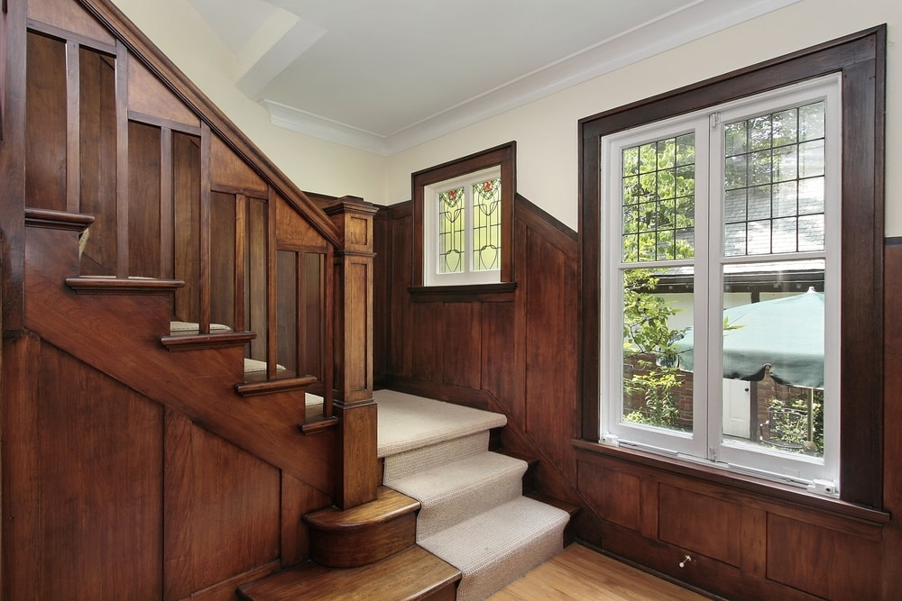 This entry features wooden walls and hardwood floors, along with a hardwood staircase with carpeted steps.