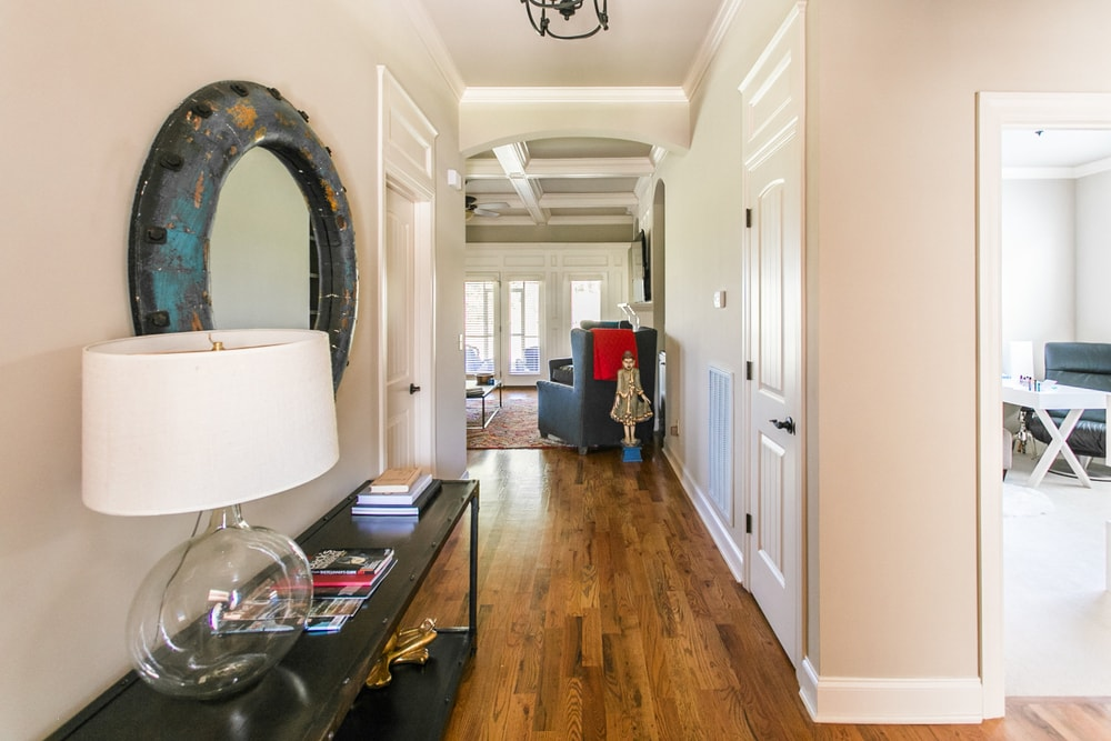 This entryway features a hallway with hardwood floors and beige walls, along with a long side table topped by a large charming table lamp.