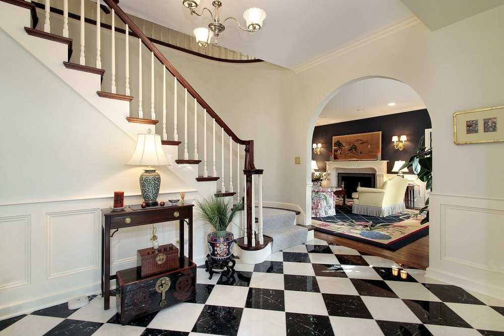 This home's entryway features classy checker tiles flooring along with a staircase with carpeted steps, lighted by a charming chandelier. The hall leads to the home's elegant living space with a large fireplace.