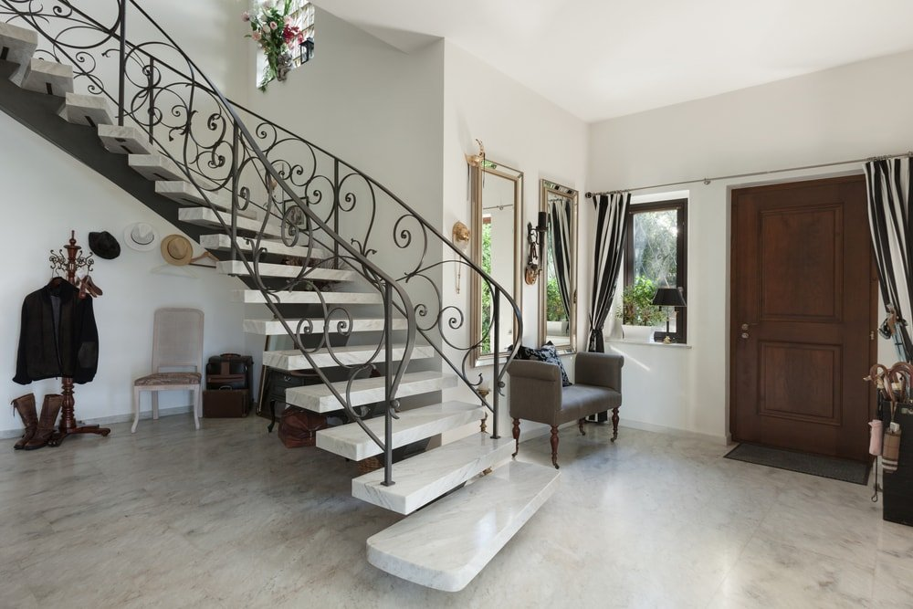 This foyer boasts an elegant curved staircase with enchanting railings design. It has stunning steps as well.