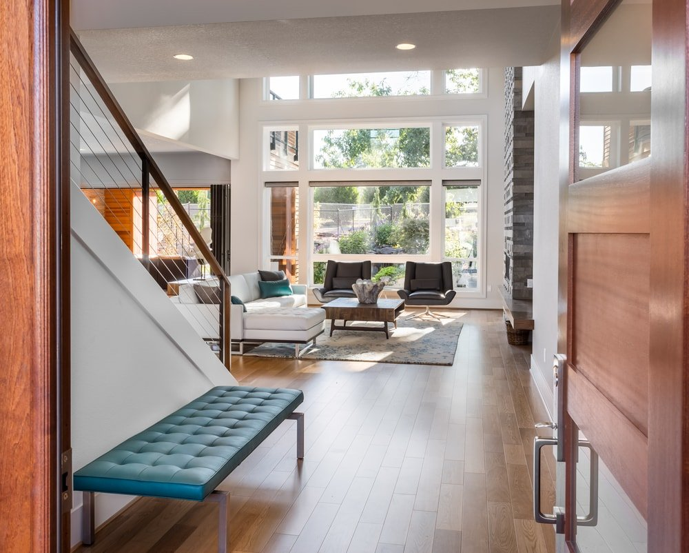 This home features an entryway leading straight to the living area boasting a modern set of furniture along with a fireplace, situated under the home's high ceiling.