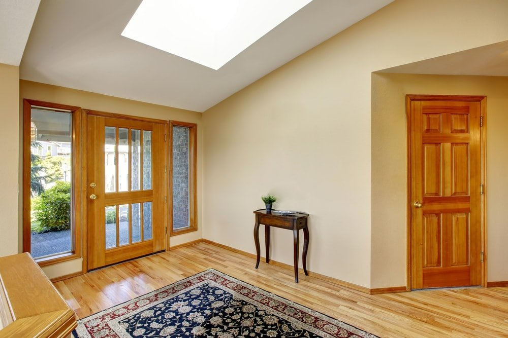 A spacious entry boasting beige walls, hardwood floors topped by an area rug and a white shed ceiling featuring a skylight.