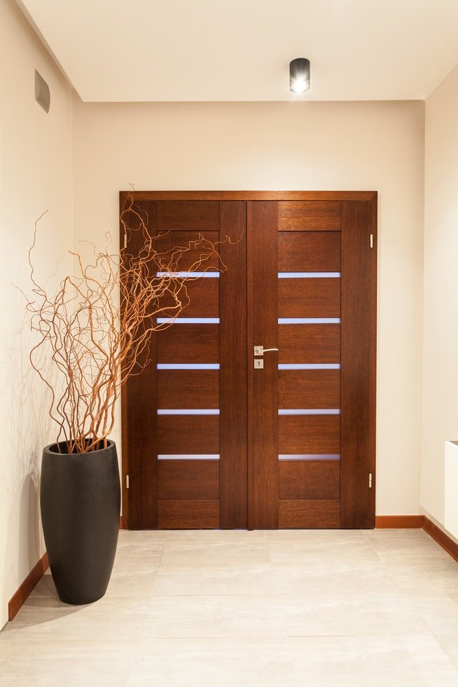 A modern home boasting an entryway with a stylish wooden door. It has tiles flooring and beige walls.