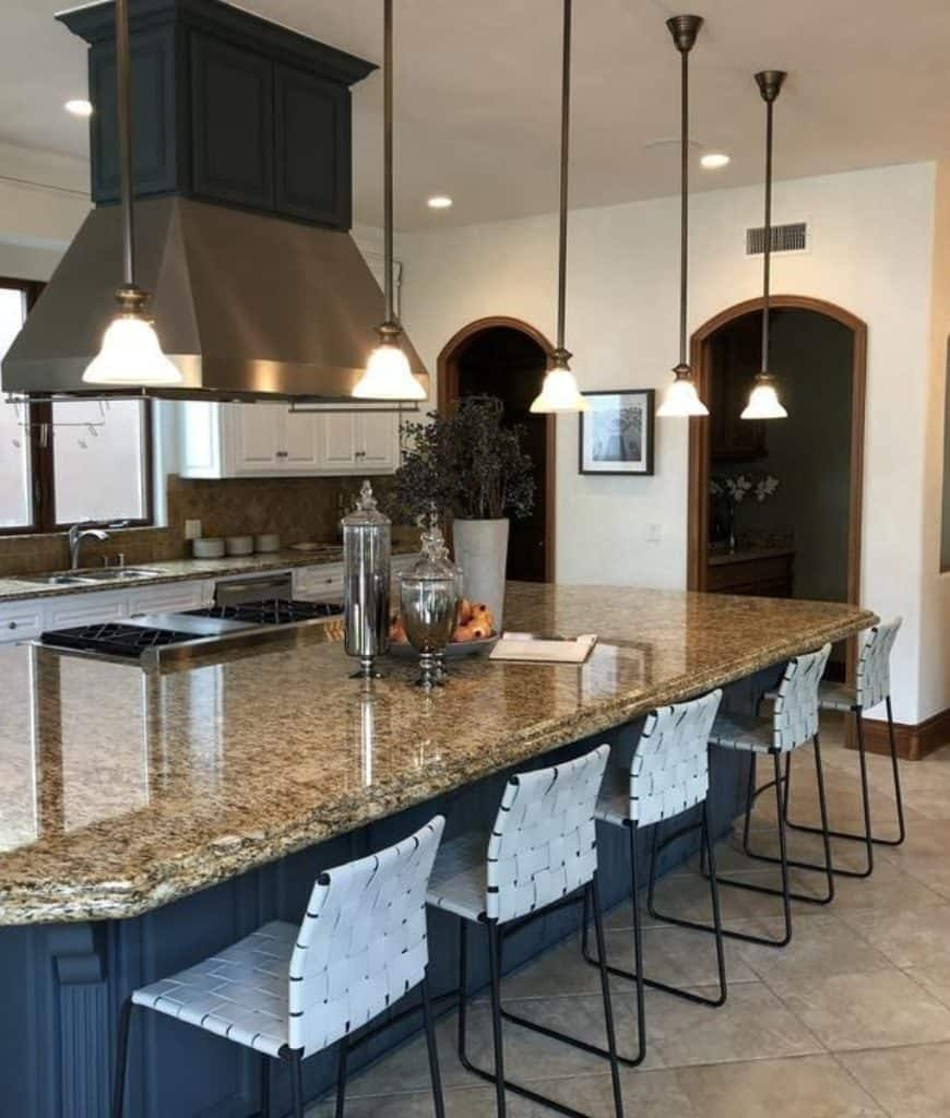 A closeup look at the spacious kitchen showcasing open archways and a stainless steel vent hood suspended over the gray island bar that's illuminated by mini glass pendant lights.