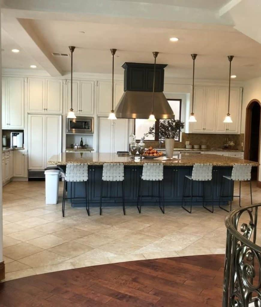 Spacious kitchen offers white cabinetry and granite top breakfast bar lined with mini glass pendant lights and white woven chairs over tiled flooring.