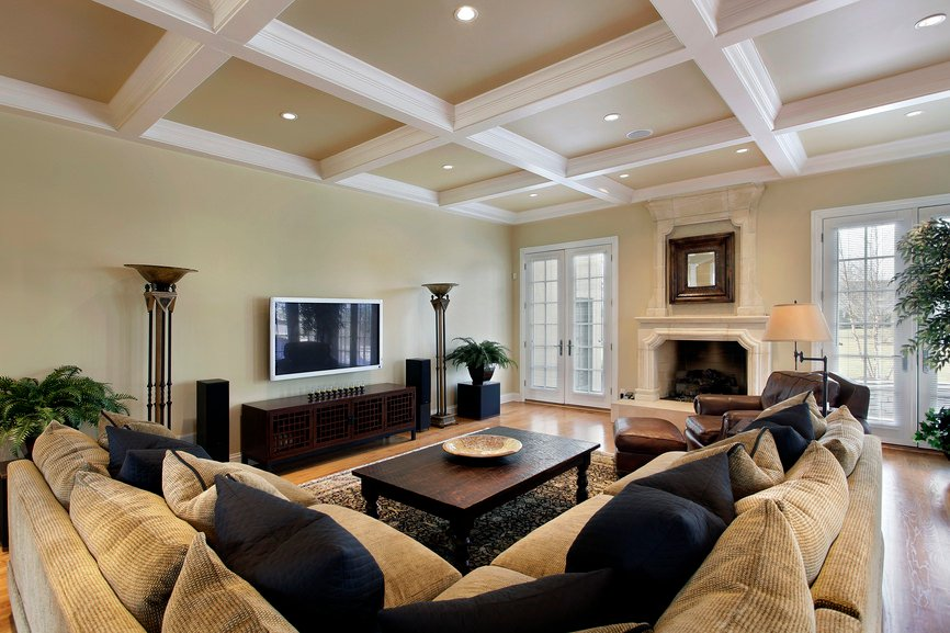 Large formal living room with a large sofa set and a fireplace along with hardwood flooring and a coffered ceiling.