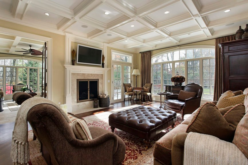 A spacious and classy living room with an elegant set of seats and a classy fireplace. The coffered ceiling is just perfect together with the home's style.