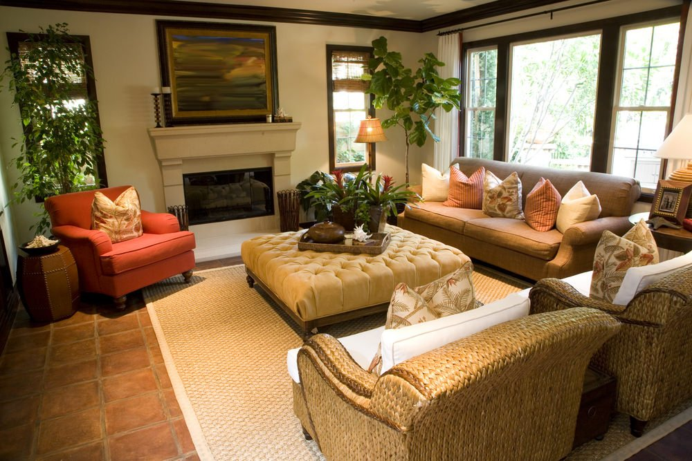 Tropical-style living room with earth-tone colors, indoor plants and wicker furniture and area rug on terracotta tile flooring.
