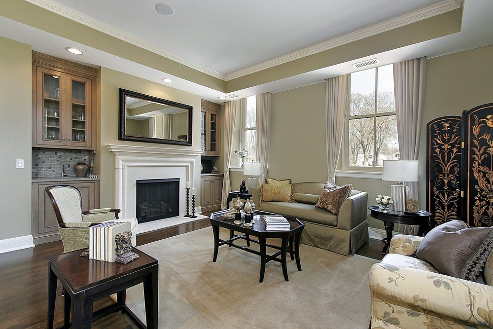 Simple yet classy formal living room with a nice set of seats and a stylish fireplace all under the tray ceiling.