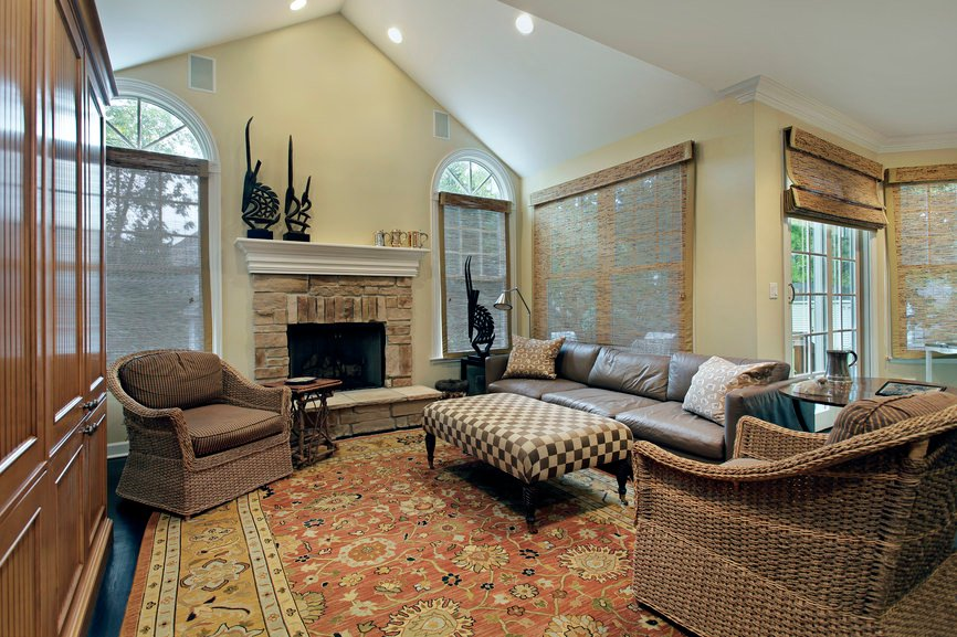 An elegant formal living room featuring a large stylish fireplace and a graceful rug covering the hardwood flooring.