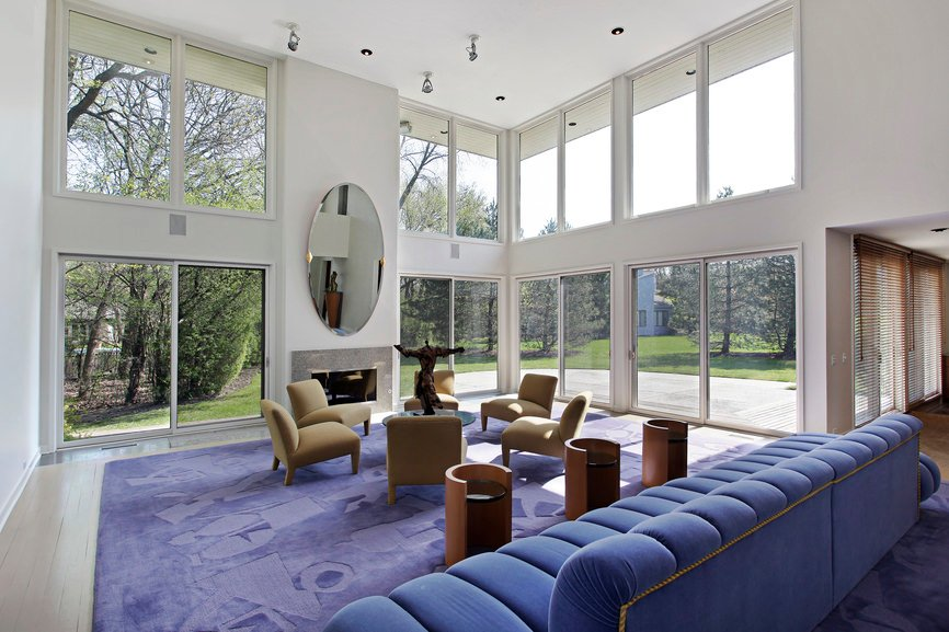 A stunning formal living room featuring white walls and high ceiling. The blue long couch looks very elegant.