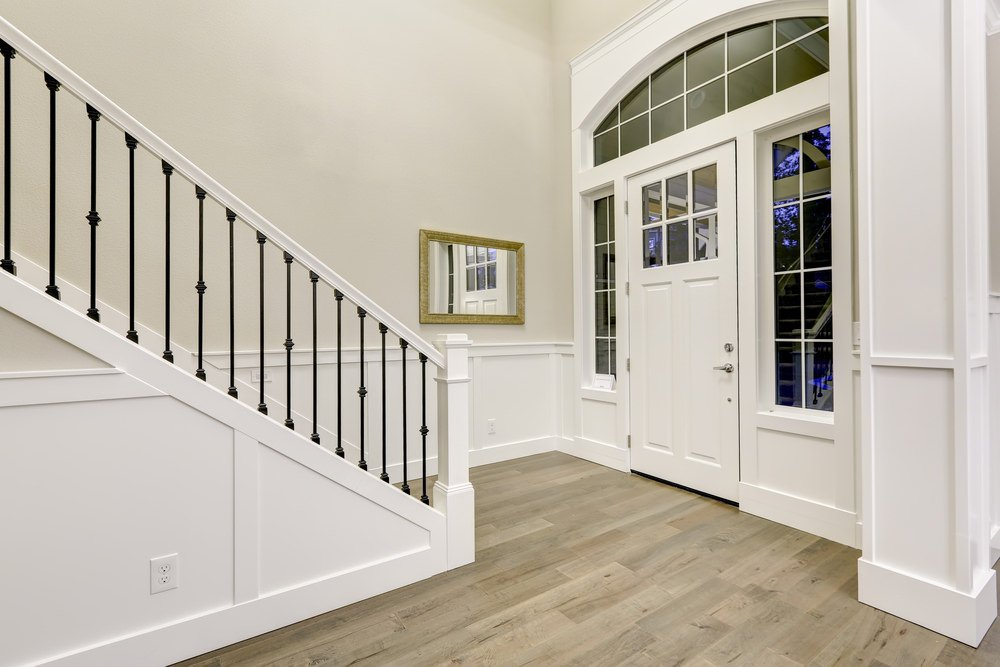 This foyer with hardwood flooring is surrounded by white walls, doors and ceiling.