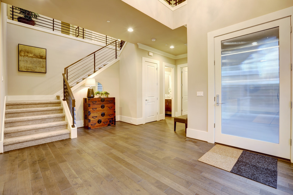 A large foyer with a wooden drawer chest at the corner and a white framed frosted glass entry door.