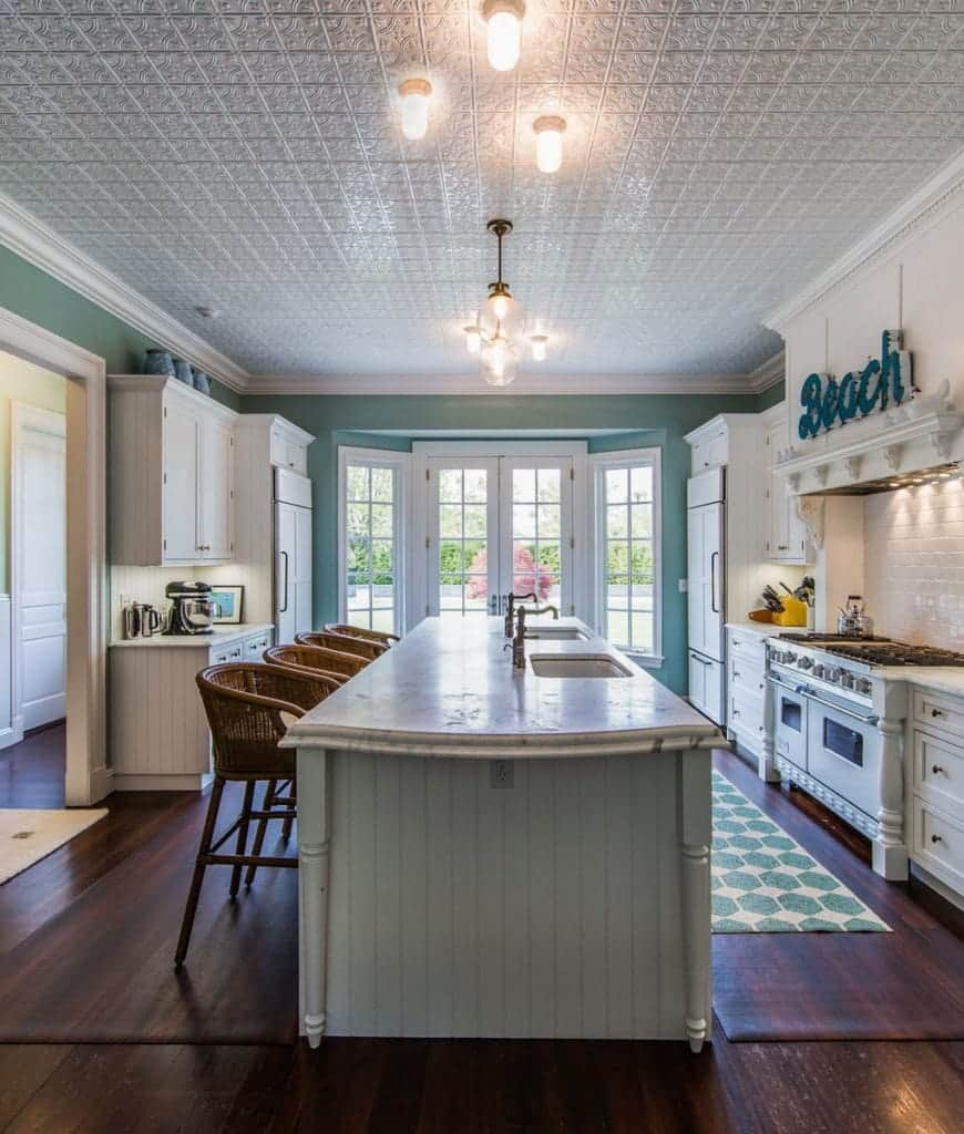 Beach style kitchen with a white French door and hardwood flooring topped by a lovely hex rug. There's a lengthy beadboard island in the middle lighted by glass globe pendants and flush lights mounted on the ornate ceiling.