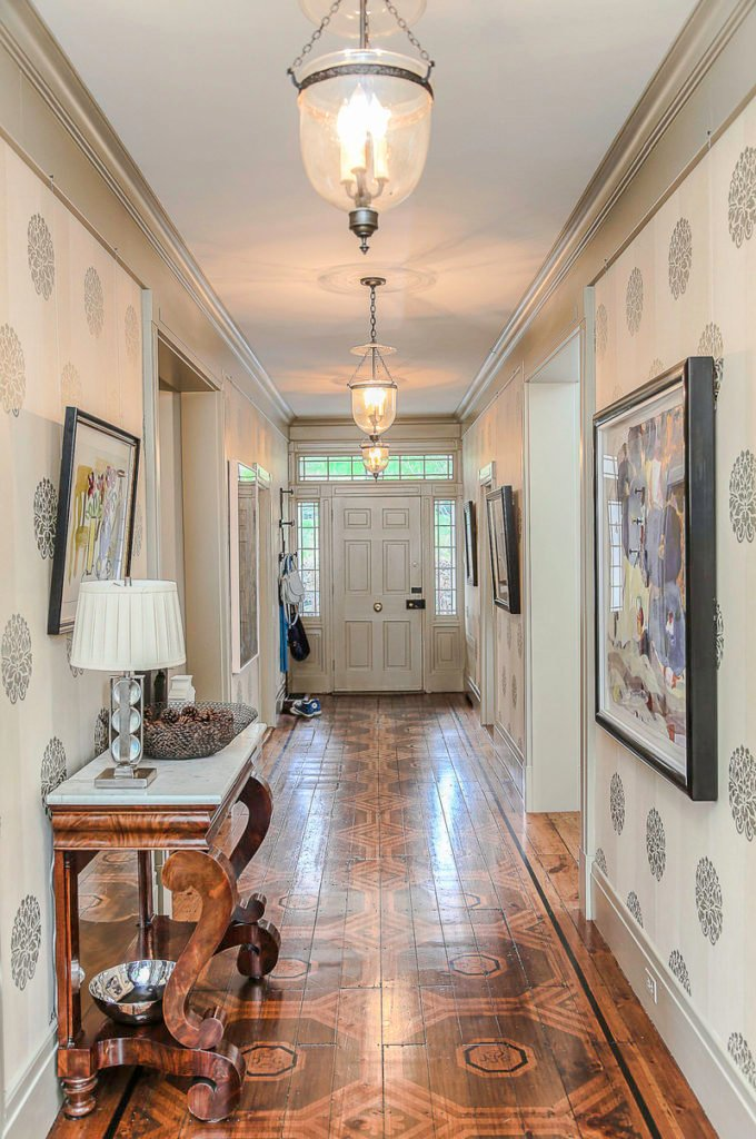 A classy entry with stylish hardwood flooring and stylish white walls along with a tray ceiling lighted by pendant lights.