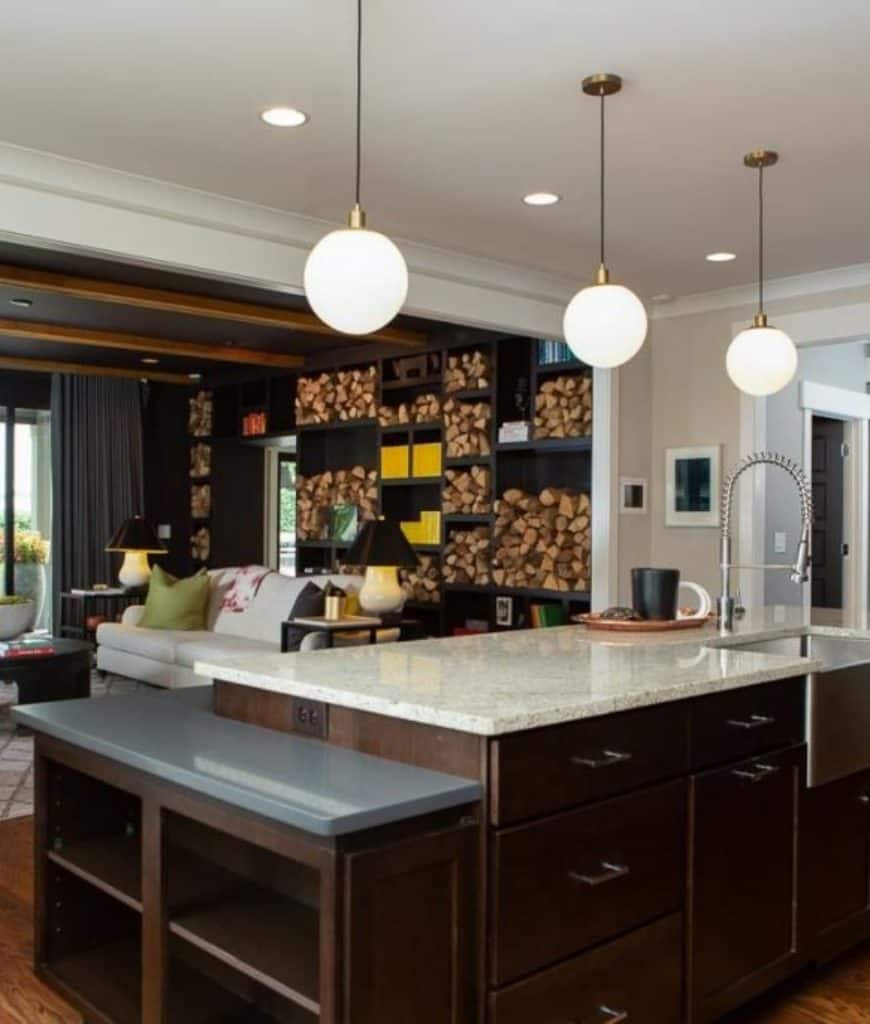 An open kitchen illuminated by globe pendant lights that hung over the wooden central island topped with granite counter and vessel sink with pull down sprayer.