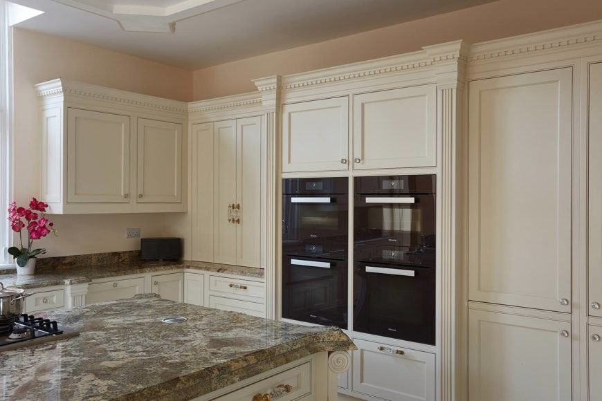 Gorgeous kitchen boasts classy beige cabinetry with glass knobs and pulls. It is fitted with a pair of double wall oven which breaks the continuity of the design and adds an exciting look.