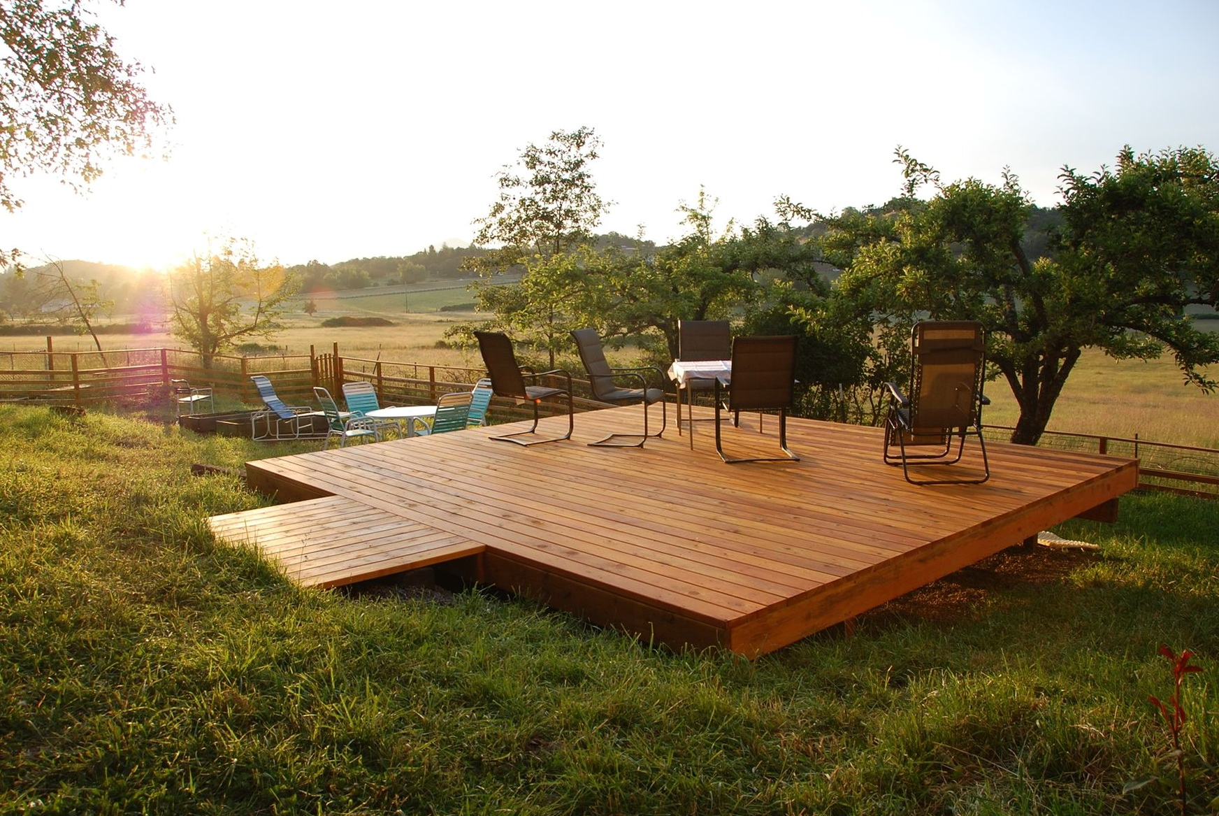This deck set on the grassland features a modern set of seats overlooking the grassland and trees spreading to a very wide distance.