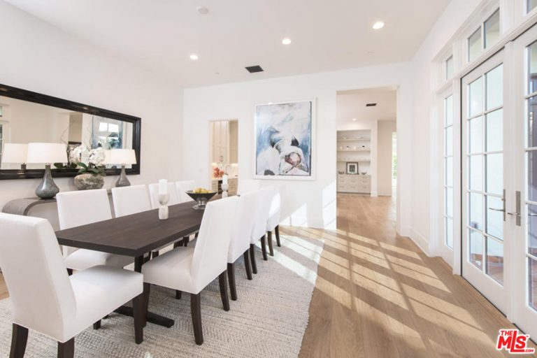 A classy white dining room featuring a long dining table set with elegant white seats set on the rug covering the hardwood flooring.
