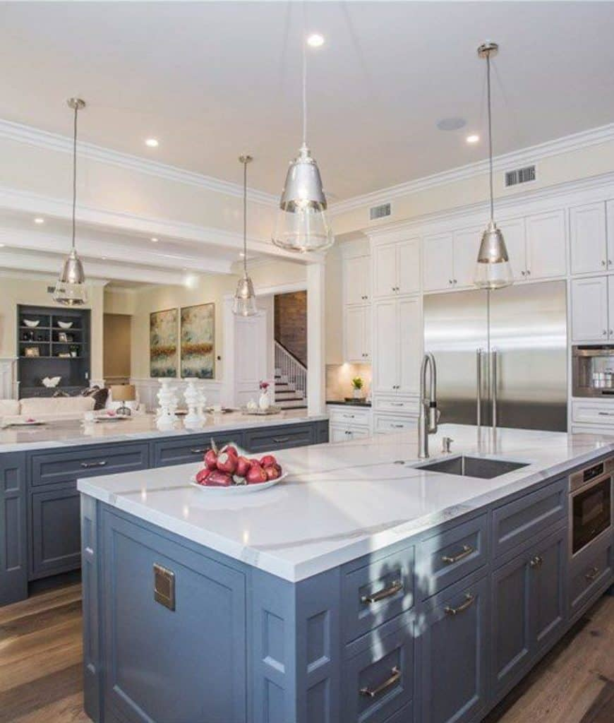 Gourmet kitchen features white cabinetry with stainless steel fridge inset and double breakfast bars on wood plank flooring fitted with sink and oven.