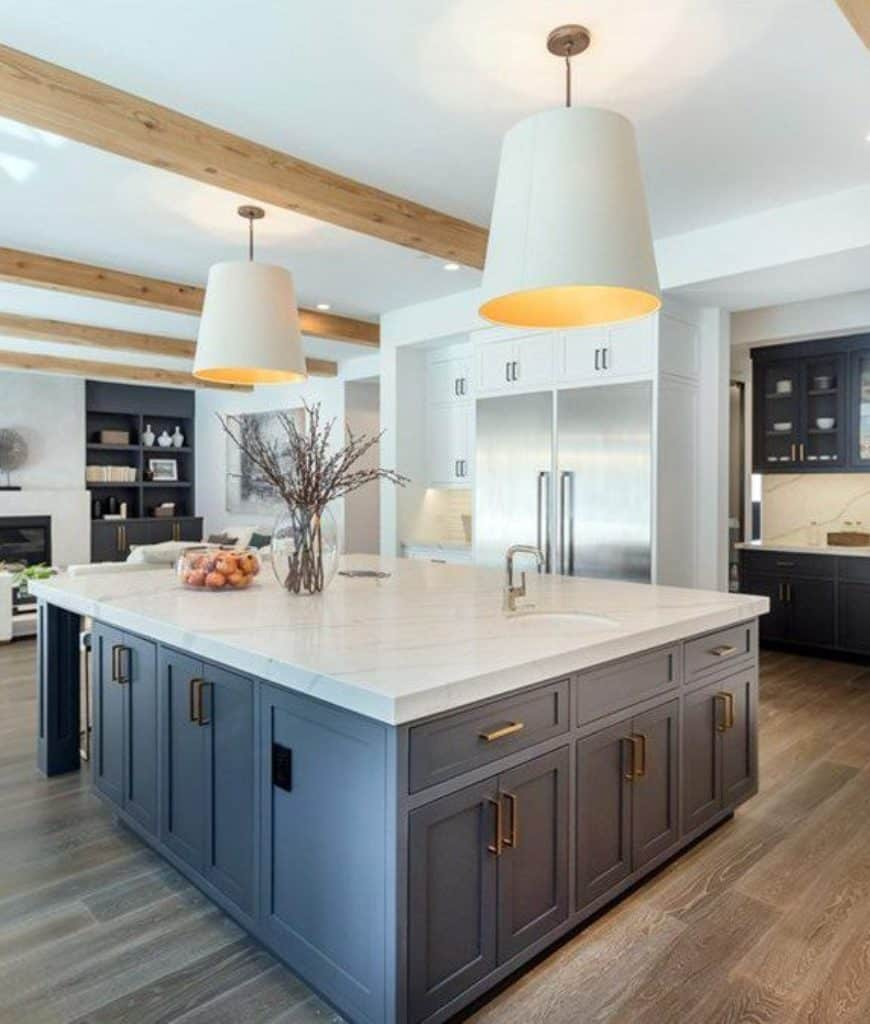 Cozy kitchen accented with gray shelving and an immense central island topped with marble counter and lighted by oversized white pendants that hung from the wood beam ceiling.