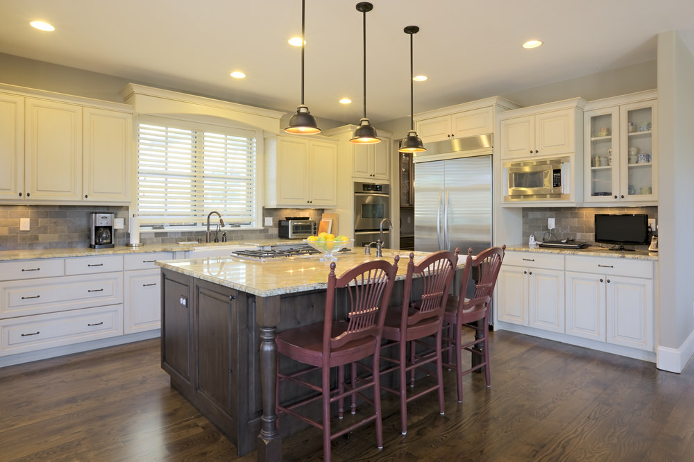 This kitchen features hardwood flooring and white kitchen counters and cabinetry. It also has a center island breakfast bar lighted by pendant lights.