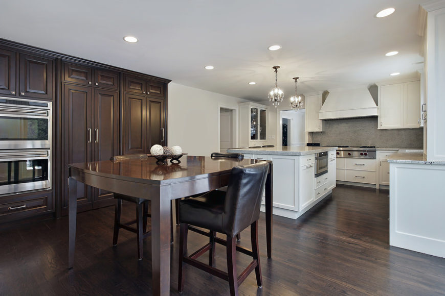 Sleek dine-in kitchen with dark wood and white cabinetry combination. It includes a wooden dining table paired with black leather chairs parallel to the white breakfast island that's lighted by crystal chandeliers.