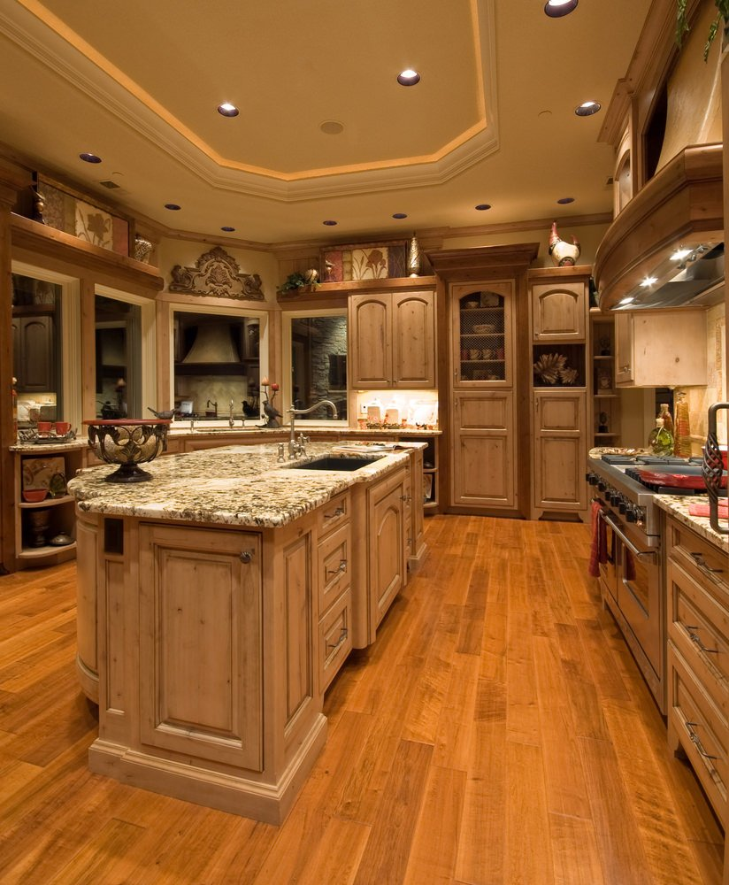 This kitchen boasts hardwood flooring and tray ceiling. The counters and center island both feature elegant countertops.