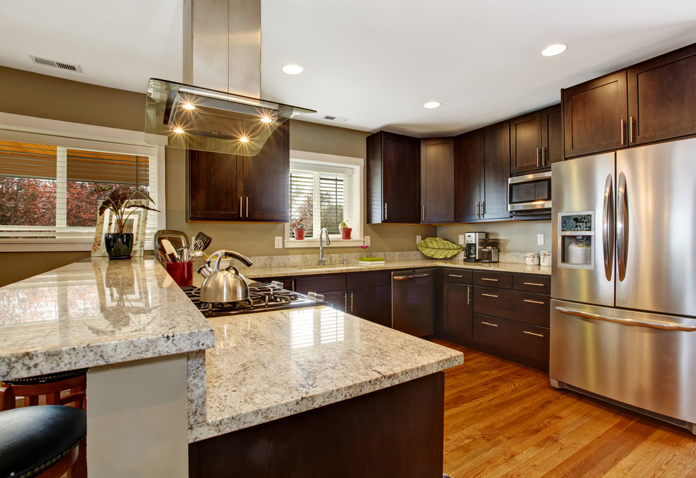 Large kitchen featuring brown cabinetry and counters along with marble countertops and classy recessed ceiling lights.