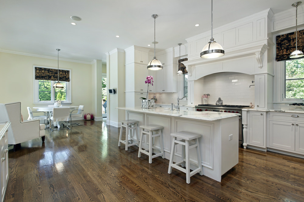 White eat-in kitchen showcases a peninsula topped with marble counter and paired with bar stools. It has hardwood flooring and glass windows wrapped in black and gold roman shades.