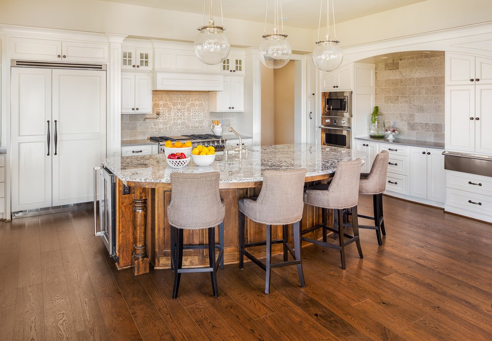 White L-shaped kitchen with breakfast island, stainless steel appliances, hardwood floors, and pendant lights.
