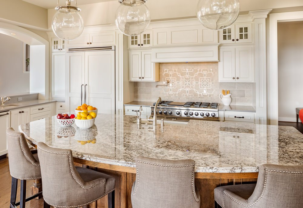 White L-shaped kitchen with huge breakfast island, hardwood floors, pendant lights, and white enamel cabinets.
