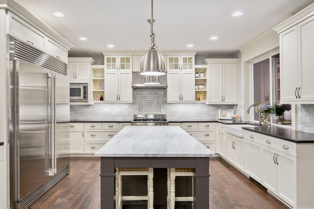 Large U-shaped kitchen boasting a large center island with a smooth marble countertop lighted by the pendant and recessed ceiling lights.