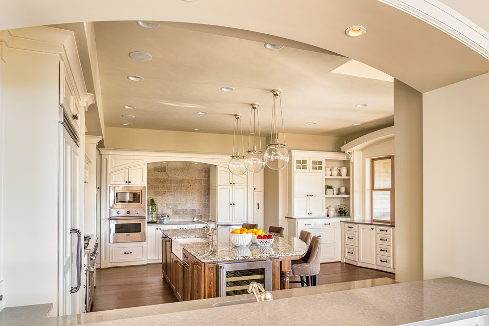 Neutral color themed kitchen with breakfast island, hardwood flooring, stainless steel appliances, and pendant lighting.