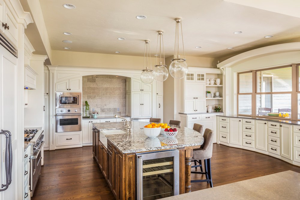 White residential kitchen with breakfast island, hardwood floors, pendant lights, and white enamel cabinets.