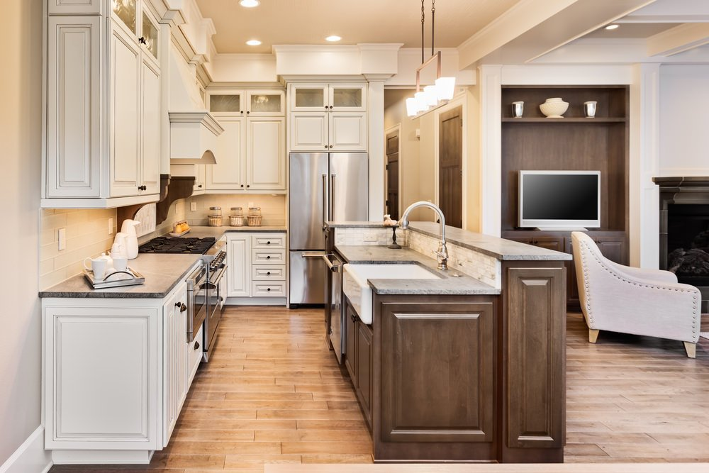 This kitchen features white cabinetry and kitchen counters, along with hardwood floors and beige walls.