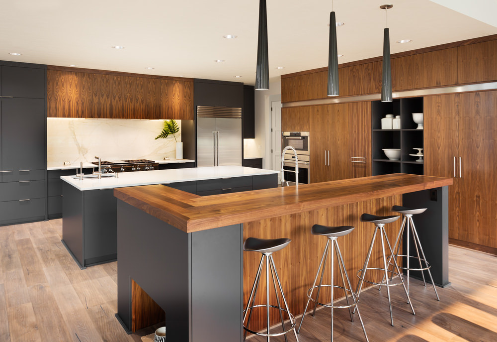 Modern kitchen with gray and brown flat panel cabinetry, white marble backsplash, a kitchen island in the middle with white countertop and gray base, and an outer L-shaped island with wood countertop, sink, and bar stools.