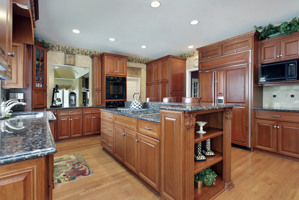 Kitchen with brown cabinetry and kitchen counters with black granite countertops together with a center island and a breakfast bar.