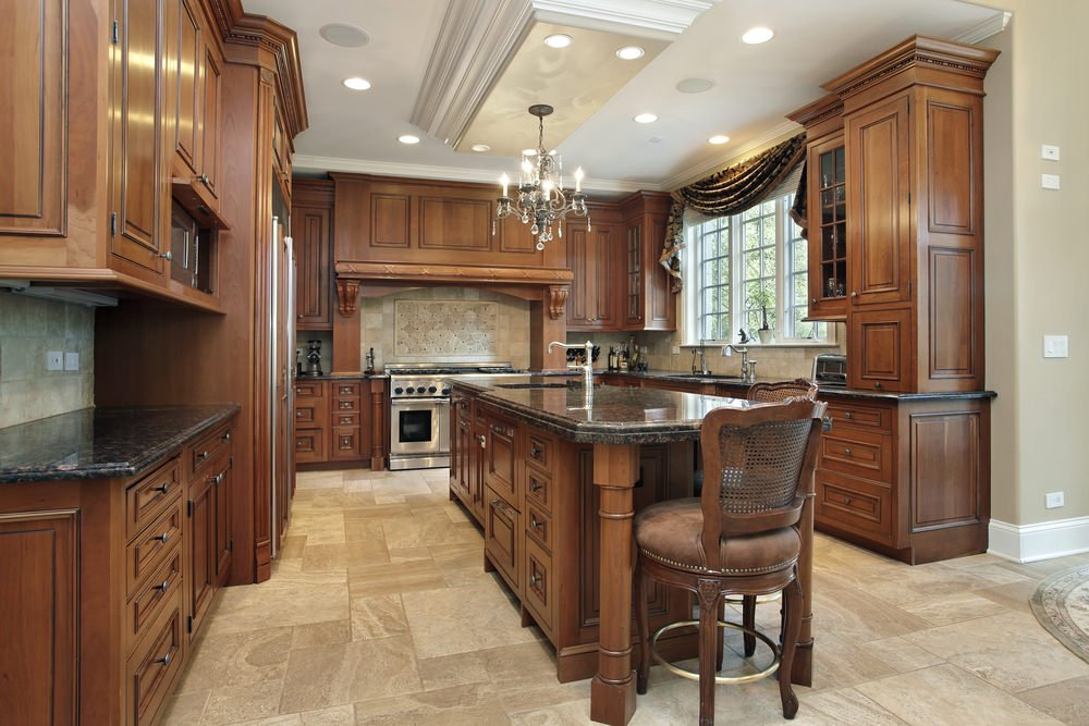 This kitchen is surrounded by brown cabinetry and kitchen counters. It also has a large center island featuring a black granite countertop similar to the kitchen counters' countertops.