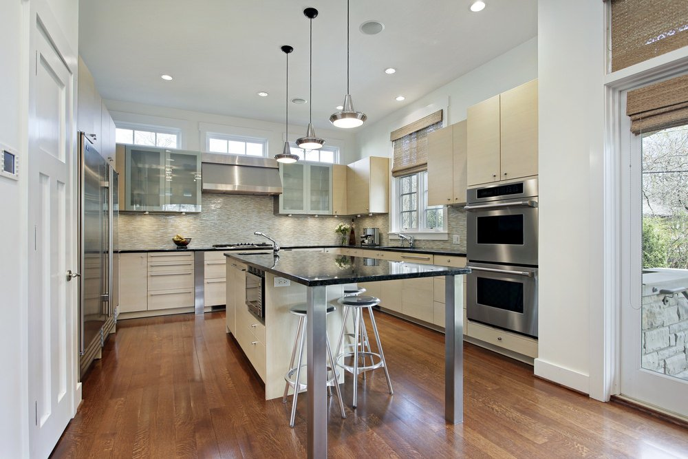 Large U-shaped kitchen featuring hardwood flooring, recessed and pendant lights.