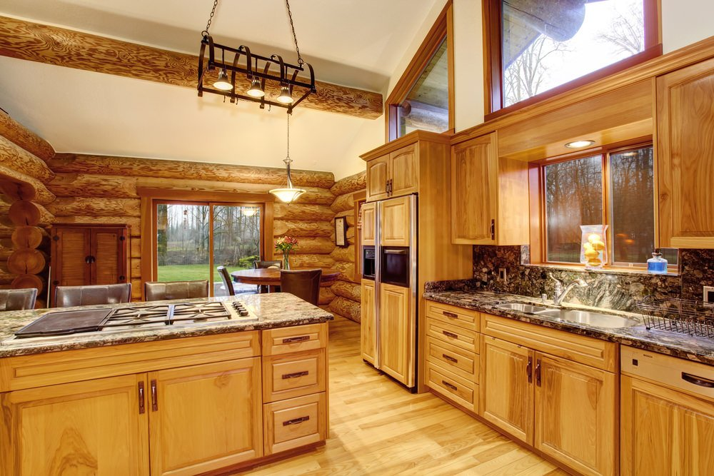 Country style log house kitchen with rustic wooden cabinetry, hardwood floors, customized wood paneled refrigerator, topped with a simple but elegant pendant light.